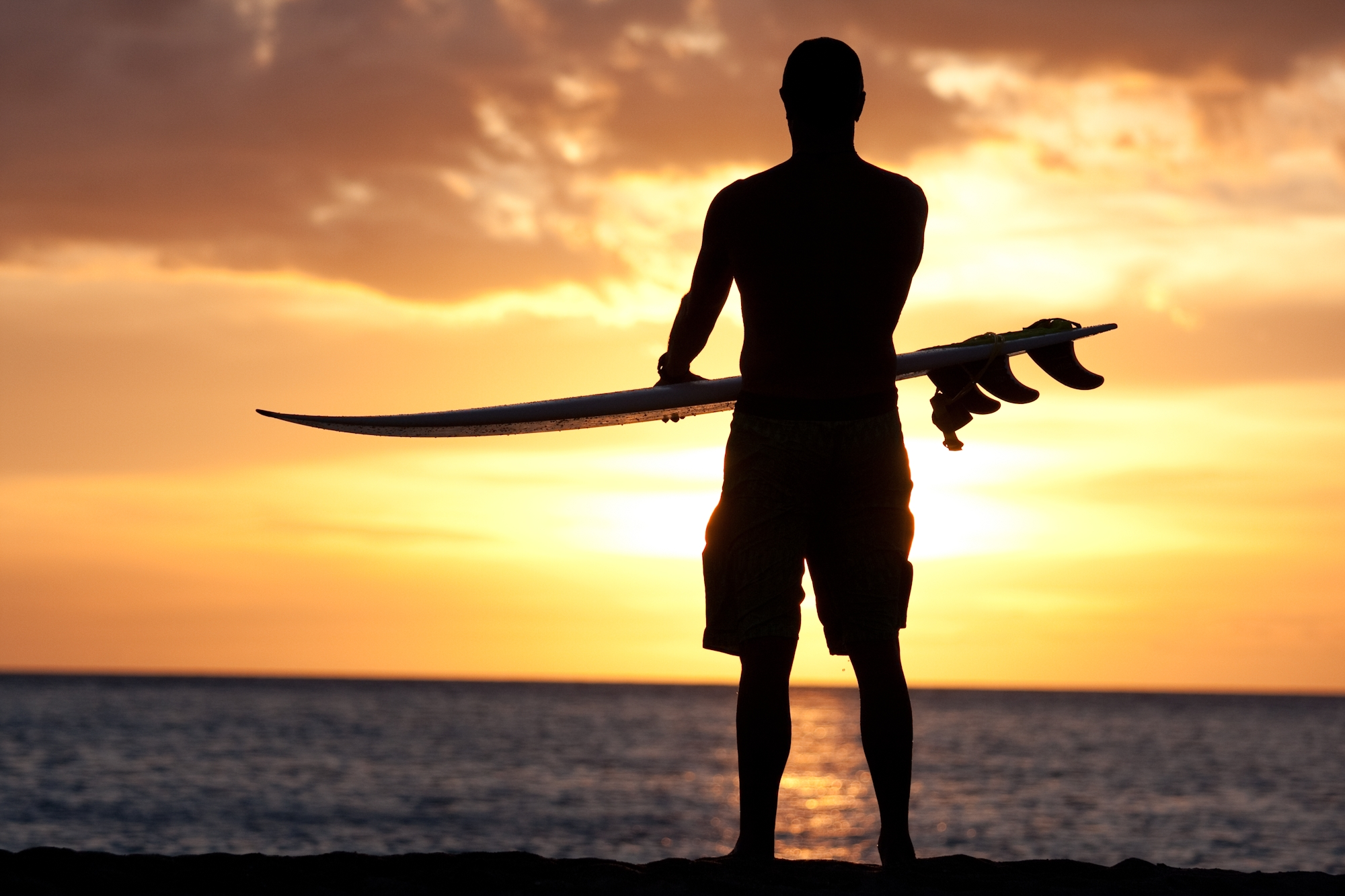 Man with surfboard on beach at sunset